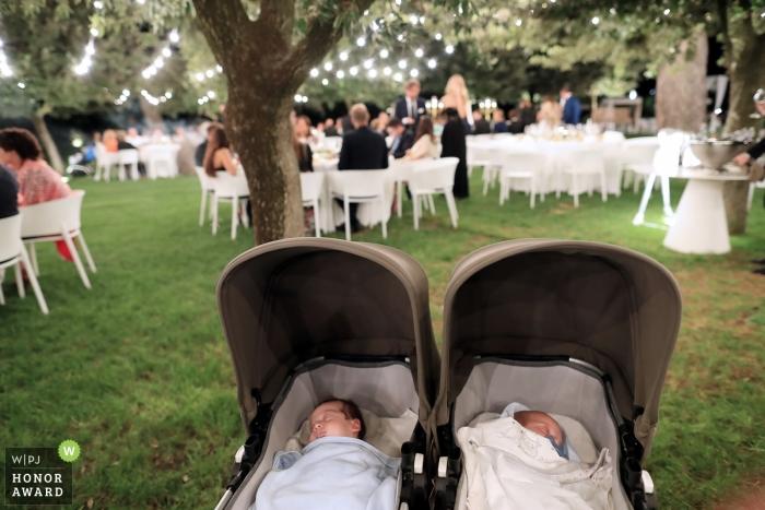 Huwelijksfoto van twee baby's in kinderwagens bij openluchtontvangst onder bomen in Puglia