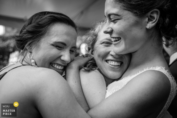 New Jersey wedding photojournalism image of a bride getting hugged by friends