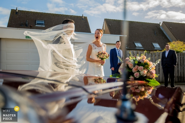 Zuid Holland wedding photography of bride's veil and groom with wind and car reflections