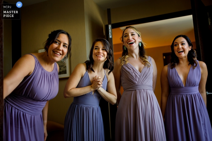 Bridesmaids react to seeing the bride in her wedding dress while getting ready at Hotel Palomar in Chicago