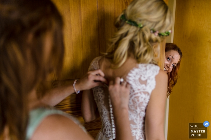 A Hesse getting ready image of the bride getting help with her dress   wedding photography in Germany