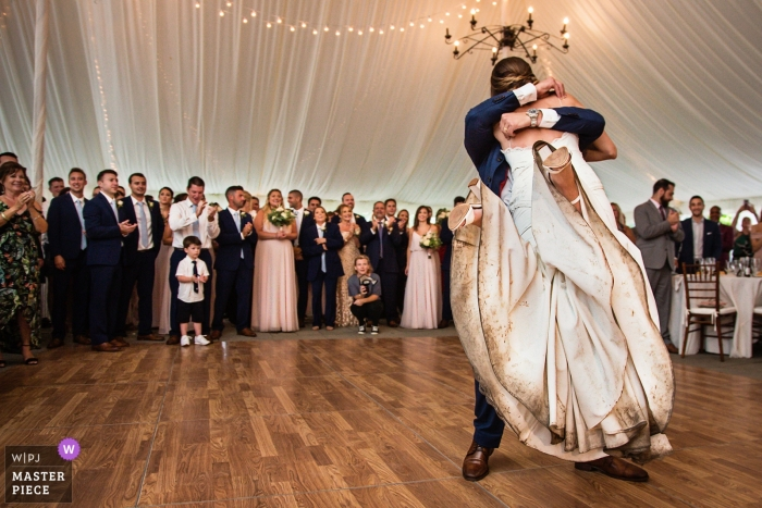 Bride with a really dirty wedding dress getting lifted up by the groom on the dance floor inside a tented reception | Crossed Keys Inn | New Jersey Wedding Photography