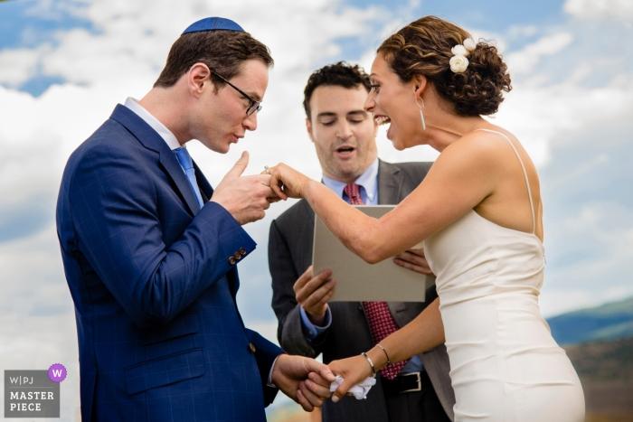 fotografia di matrimonio in Colorado di sposo in procinto di baciare la mano della sposa durante la cerimonia