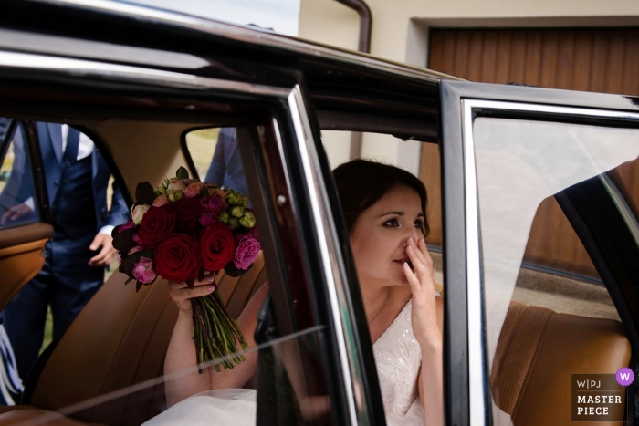 Poland, Gdansk wedding photograph of bride in the car with her flowers | bride at home before the ceremony