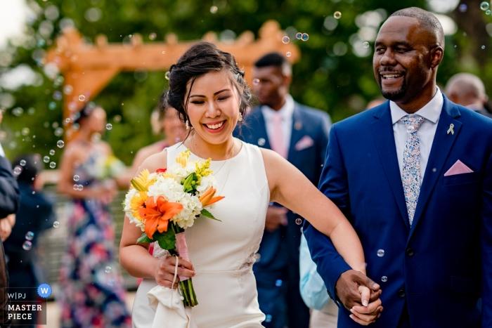 Sposa e sposo che camminano fuori dopo cerimonia al Riverview a Accoquan, Lorton, in Virginia