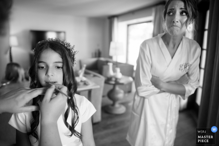 A Phoenix bride watches flower girl having makeup applied during getting ready image | AZ wedding photography