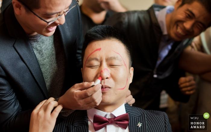 Photographie de mariage Shaanxi - Ville de Weinan, Chine, des amis ont utilisé du rouge à lèvres pour peindre le maquillage du visage sur le visage du marié, ce qui a rendu tout le monde très heureux.