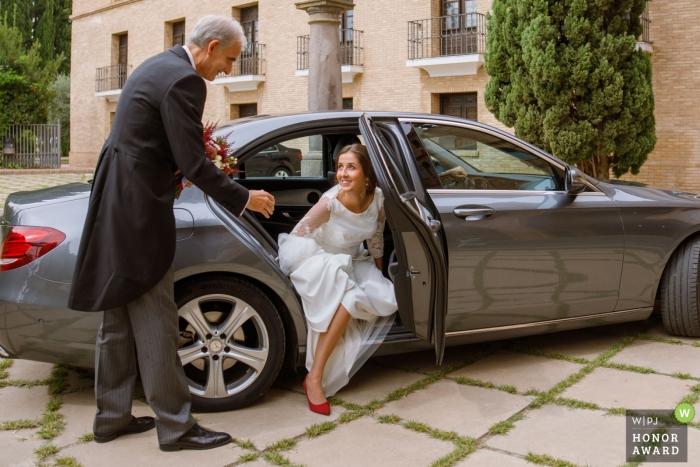 Fotografia ślubna w Saragossie | fotografia ślubna Bride przyjeżdża do kościoła, wychodzi z samochodu z pomocą ojca