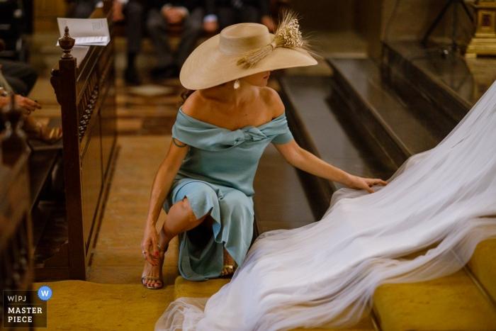 Demoiselle d'honneur dépliant le voile dans l'église lors d'une cérémonie | Aider la mariée à Saragosse, en Espagne