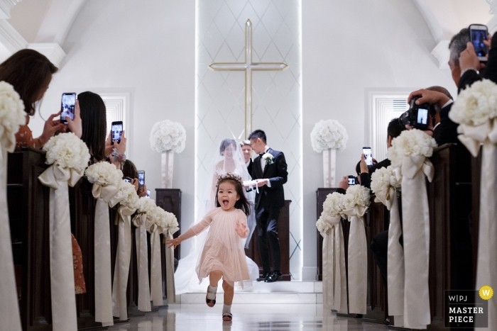 wedding photograph of little girl running out the aisle from Shandong, China | wedding ceremony