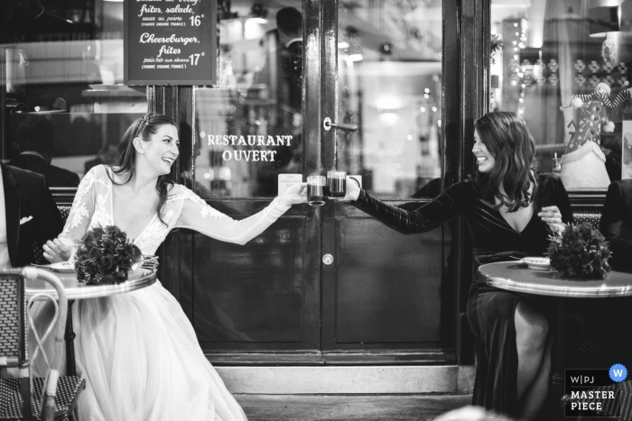 Wedding photograph of bride toasting at coffee shop with girlfriend   Wedding day moments captured in Paris, France