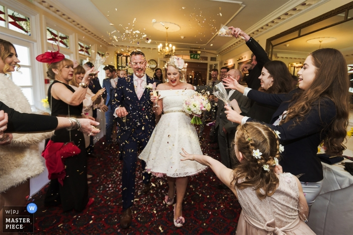Flower girl and guests throw confetti at bride and groom - Devon England Wedding ceremony at Two Bridges Hotel