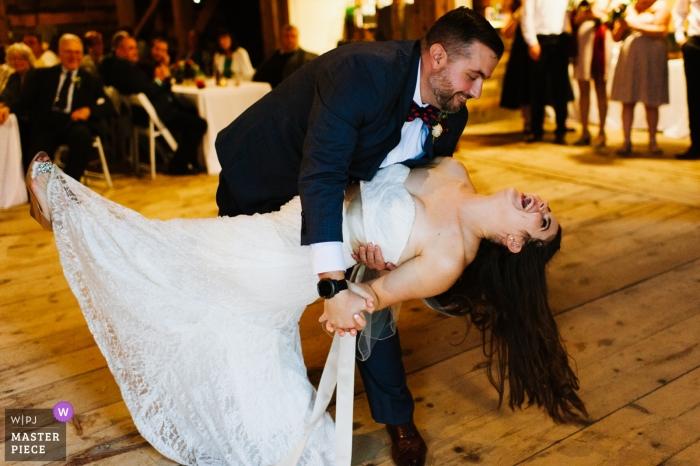Un marié plonge une mariée lors de leur première danse dans une grange lors de la réception de leur mariage - Joyful First Dance