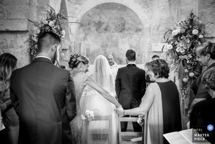 Hochzeitsfotografie in Apulien | Braut hält Hände mit Mutter während der Zeremonie