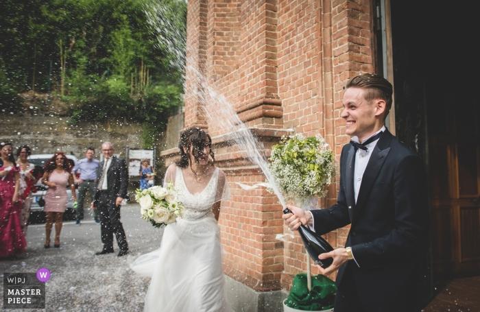 Turin wedding reception photography | groom spraying champaign outside church in Racconigi