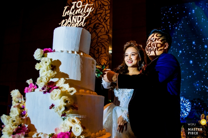 """Ho Chi Minh wedding cake cutting ceremony - super groom transfiguration with """"to infinity and beyond"""" shadowed on his face"""