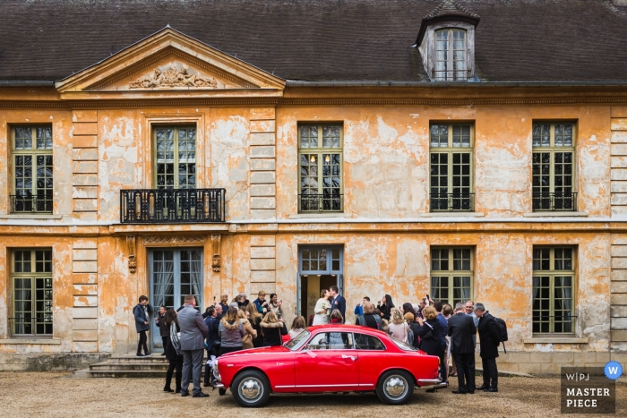 Paris Ceremony photograph of a red car, the bride and groom, and guests