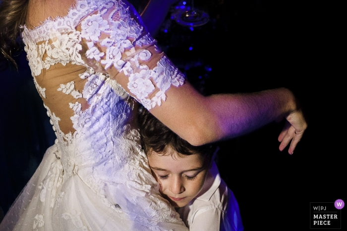 The bride gets a hug from a small boy at Tribuna B, Jockey, Rio de Janeiro, Brazil during the wedding party