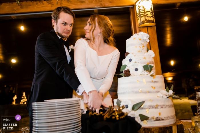 La novia y el novio reaccionan casi derribando su pastel de bodas mientras lo cortan durante su recepción en Elkins Resort en Priest Lake en Nordman, Idaho.