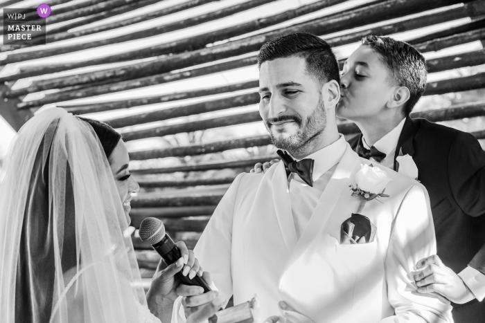 Cérémonie de mariage au Royalton Riviera Cancun Resort - Le fils s'embrassant est papa pendant que la mariée parle dans un micro