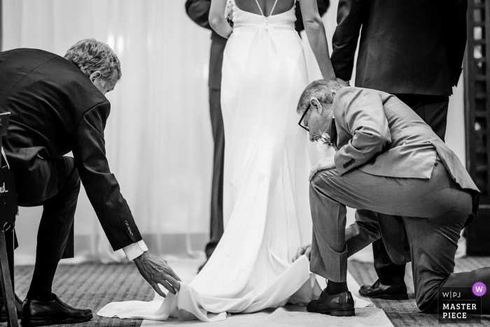 chicago wedding ceremony photograph of the bride getting dads' help with her dress train