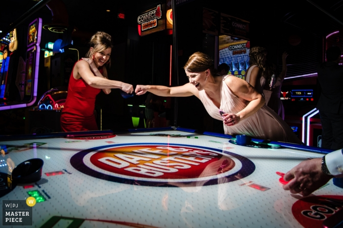 Elkhorn, NE Wedding Party knucks after scoring a goal during an air hockey match
