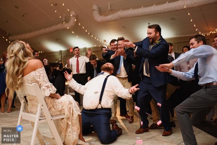 Sanderling Resort, Duck, NC, Hochzeitsfotograf - Groomsmen schenken dem Bräutigam Zuckerpakete, während er das Strumpfband der Braut entfernt.