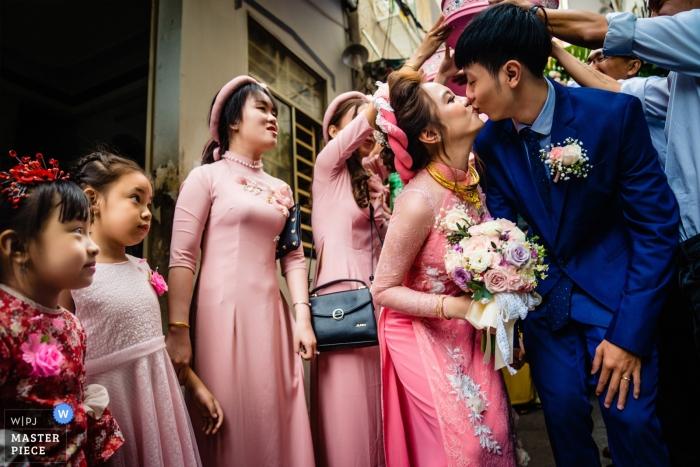 Rituales del día de la boda de Vietnam Cantho: rostros sorprendidos de los niños y la pareja que se besan afuera