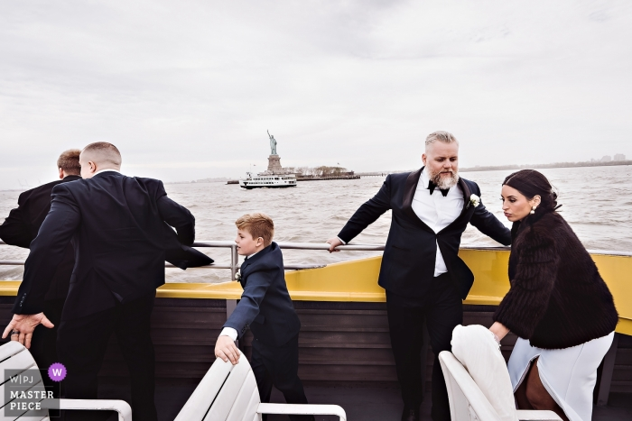 The Liberty Warehouse, NY wedding boats - photographer caught Guests, Bride & Groom trying not to loose balance on watertaxi
