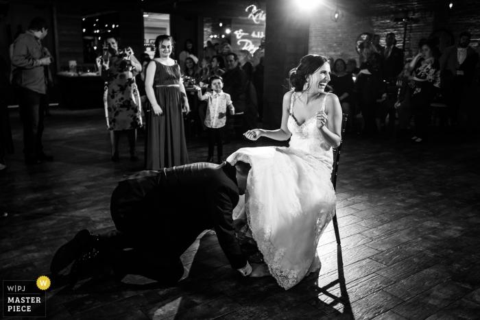 biagio evants huwelijksfotografie | kouseband dansen om te beginnen met de bruidegom vissen de kousenband van onder de jurk van de zittende bruid