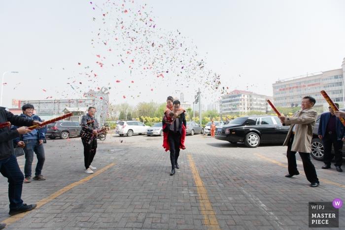 Fotografia ślubna TianJin - święto z konfetti armatnimi i pan młody niosący dziewczynę