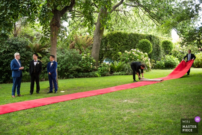 Melbourne wedding photographer - preparing the long red carpet on the grass for the outdoor ceremony - Bride on the way