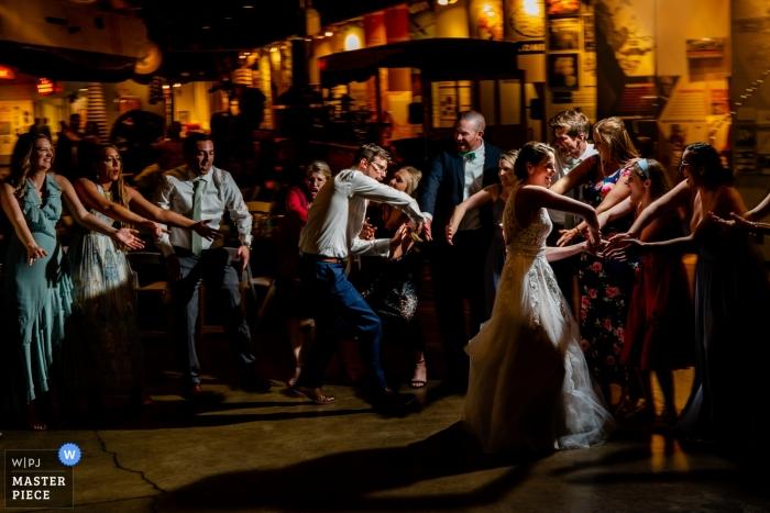 Fotografo di matrimoni al Baltimore Museum of Industry, Baltimore, MD | Alto cinque e basso cinque per gli sposi sulla pista da ballo della reception.