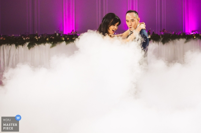 Curzon hall, Sydney, Australia wedding photographer | Groom and bride being shocked at first dance after seeing the fog on the floor that they didn't expect.