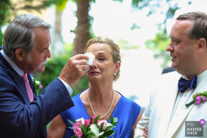 Wedding photographer for the Casa Hyder | The groom's father wipes his wife's tears as their son (the groom) watches.