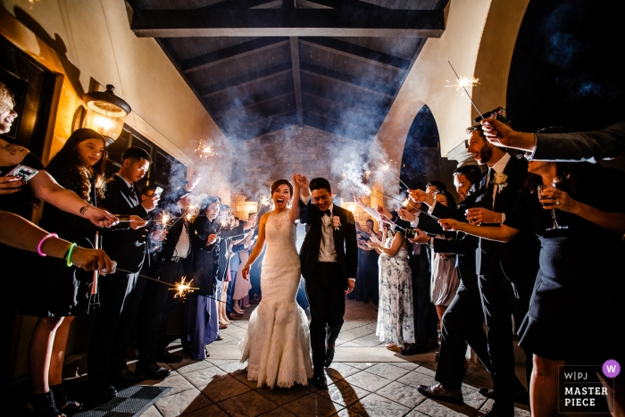 Foto de la novia y el novio saliendo y paseando a través de los invitados que sostienen luces de bengala por un fotógrafo de bodas en Lake Tahoe, California.