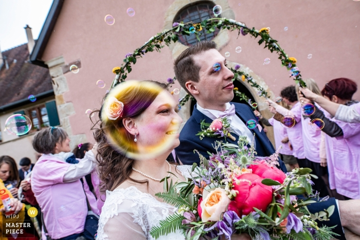 This Rouffach, France wedding photographer has captured a photo of the bride through a bubble as she walks with her groom.