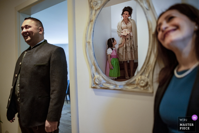 Guests get their first look at the bride, reflected in the mirror, before her Austrian wedding in this photo by a Calabria wedding photographer.