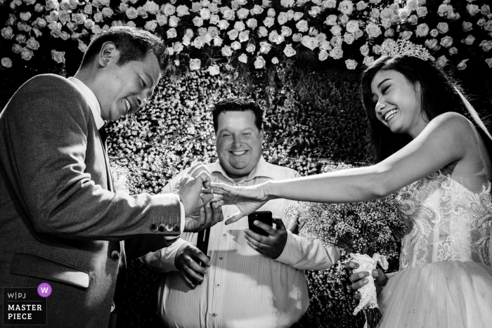 The bride and groom exchange rings at the altar decorated with flowers in this black and white photo by a Ho Chi Minh, Vietnam wedding photographer.