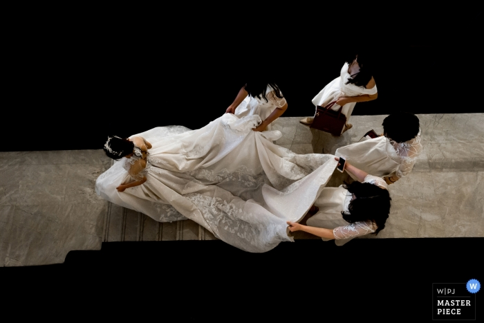 Druhny pomagają pannie młodej w sukience, idąc po schodach hotelu w kierunku ceremonii na tym zdjęciu autorstwa fotografa ślubnego z Fujian w Chinach.