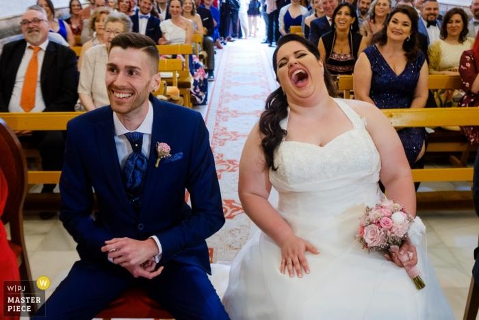 Los novios sonríen y ríen mientras se sientan en el altar en Santa Pola en esta foto de un fotógrafo de bodas de Alicante, Valencia.