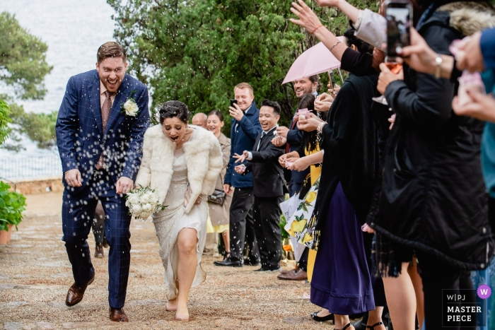 Photo of rice throwing at the bride and groom after the ceremony at El Convento de Blanes