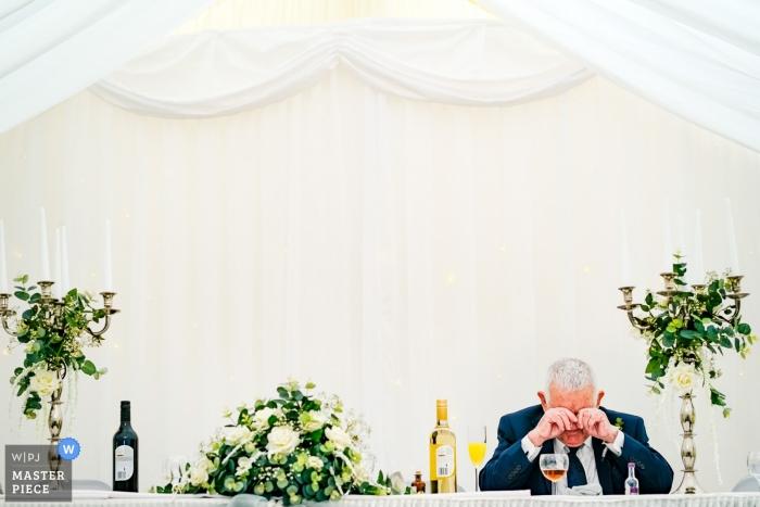 De grootvader van de bruid neemt een moment alleen tijdens de bruiloftsreceptie op een bruiloft in Southampton, Engeland
