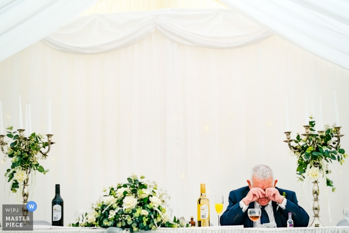 The grandfather of the bride takes a moment by himself during the wedding reception at a Southampton, UK wedding