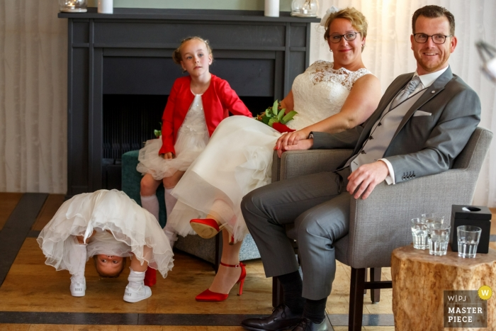 A young girl gets another point of view of the wedding as she peeks between her legs while the bride, groom, and another young girl pose for this portrait by a Hellendoorn, Netherlands wedding photographer.