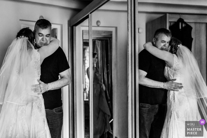 Auxerre father hugging his daughter, the bride, on wedding day. Getting ready photography.