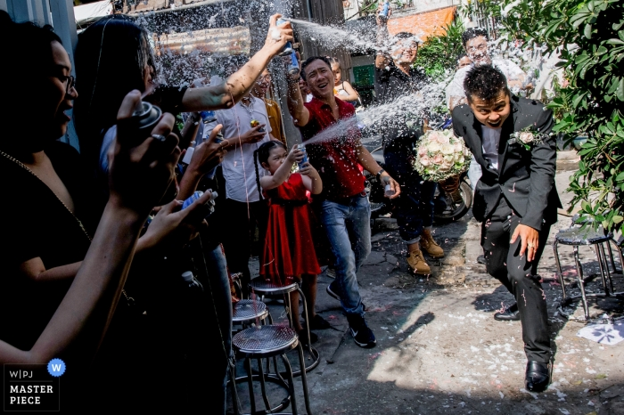 Photo of the groom making his way past guests as they spray him with foam spray by a Ho Chi Minh, Vietnam wedding photographer.
