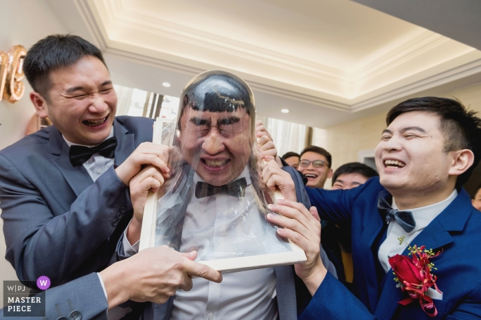 The best man plays a game with the other groomsmen in the living room of a Fuzhou home in this photo by a China wedding photographer.