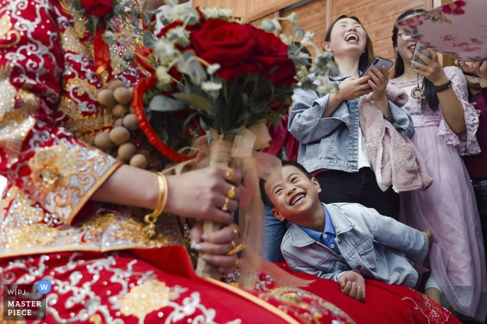 Photo of a young boy admiring the bride's colorful dress and bouquet at a Fuzhou home by a China wedding photographer.