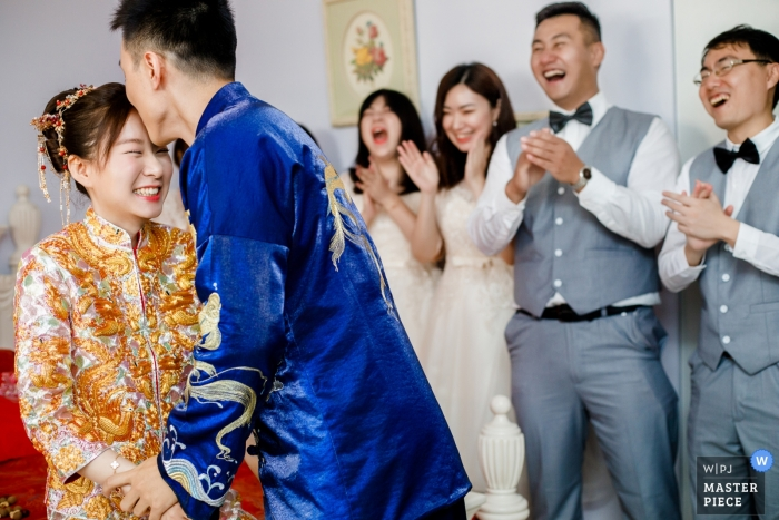 wanda hotel wuhan china | The groom kisses the bride as friends cheer for him on actual wedding day.